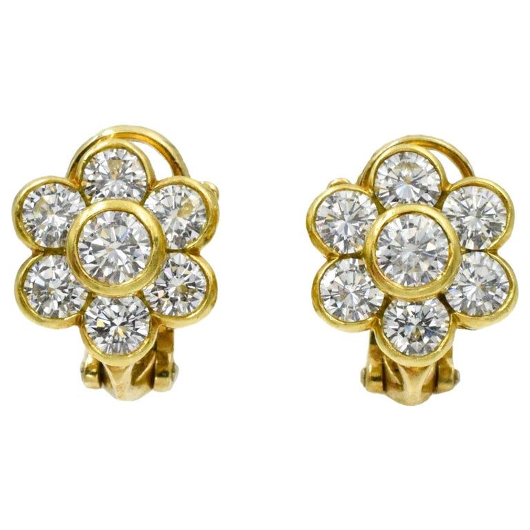 Van Cleef and Arpels Diamond Flower Earrings. This pair of earrings has 14 roound diamonds with a total carat weight of approximately 2.6 carats all bezel set in 18k yellow gold with omega back.  Signed Van Cleef & Arpels Serial No. NY xxxxx,