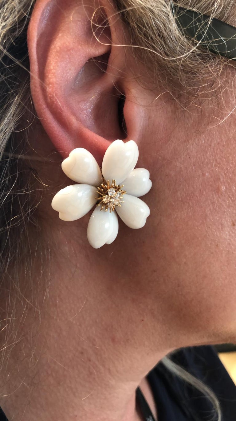 The iconic Rose de Noel earrings by Van Cleef & Arpels, each designed as a coral flowerhead with 18k yellow gold wirework pistils surrounding a brilliant-cut diamond cluster centre.  Dimensions approx.  length 1 1/2