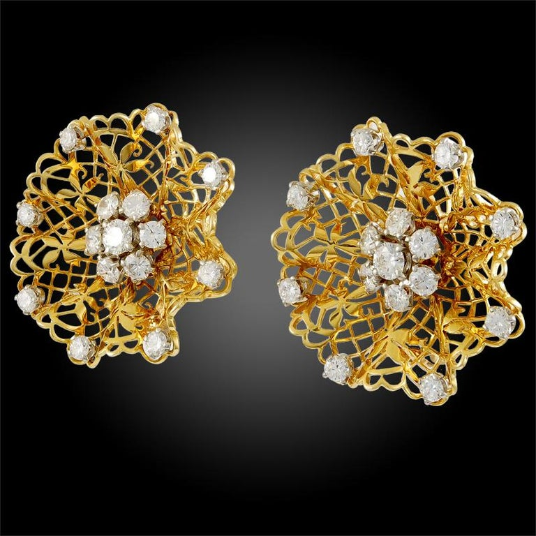 A quintessentially feminine and elegant pair of openwork lace-like ear clips by Van Cleef & Arpels that dates back to the 1940s, finely crafted in 18k yellow gold, centering luminous round cut diamond clusters further accented at the edges by round