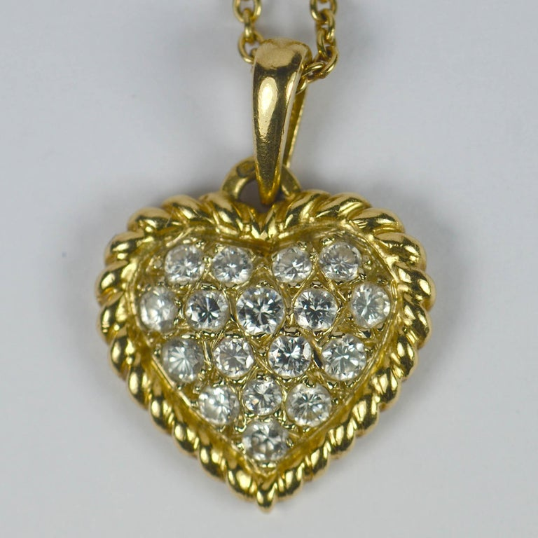A classic pave diamond set heart pendant on a fine 18kt yellow gold chain necklace by Van Cleef & Arpels. The heart is set with 17 brilliant round cut diamonds (VVS clarity, E-F colour) enclosed by a rope-twist gold border, with a total diamond