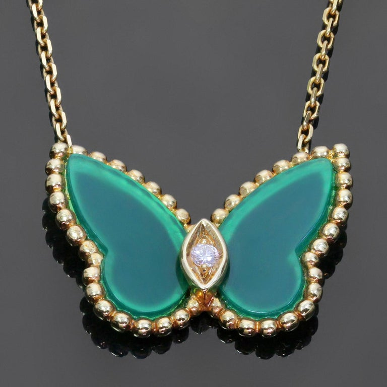 This iconic Van Cleef & Arpels necklace is crafted in 18k yellow gold and features a butterfly shaped pendant suspended from a link chain and accented with green chalcedony wings and a brilliant-cut round diamond of an estimated 0.03 carats. Made in