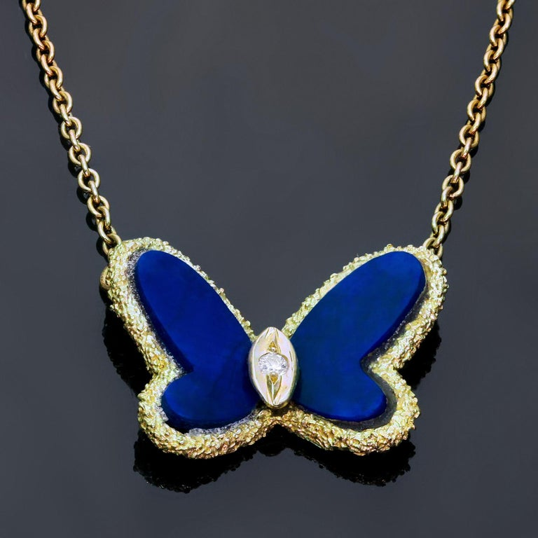 This iconic Van Cleef & Arpels necklace is crafted in 18k yellow gold and features a butterfly shaped pendant suspended from a link chain and accented with blue lapis lazuli wings and a brilliant-cut round diamond of an estimated 0.03 carats. Made