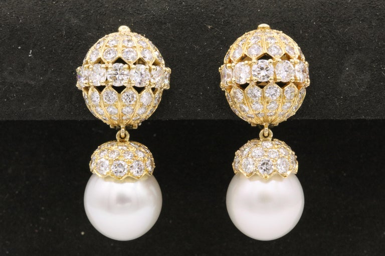 Van Cleef & Arpels cultured pearl and diamond earclips. The two cultured pearls measure approximately 12.5 mm, capped by round brilliants. Signed: Van Cleef & Arpels, numbered 2402 S.O.; Circa 1965  Comes with Paperwork and pouch.  Property of