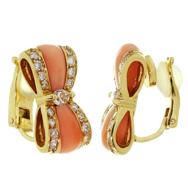 These exqusite vintage clip-on Van Cleef & Arpels earrings are crafted in 18k yellow gold and feature a bow-shaped design set with pink coral and brilliant-cut round E-F VVS1-VVS2 diamonds weighing an estimated 1.16 carats. Made in France circa