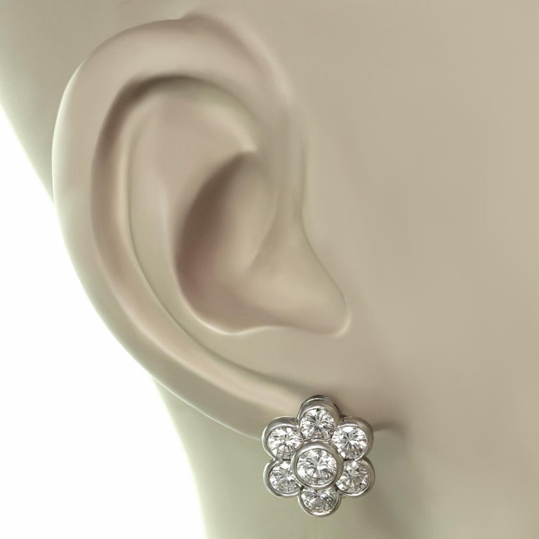 These beautiful Van Cleef & Arpels earrings feature a six petal design crafted in platinum and bezel-set with brilliant-cut round E-F-G VVS1-VVS2 diamonds - the two center diamonds weigh an estimated 0.50 carats and the 12 surrounding diamonds weigh