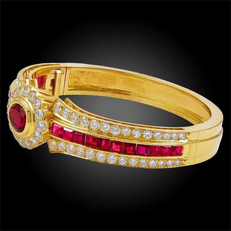 """A quintessentially elegant bangle by Van Cleef & Arpels, crafted in 18k yellow gold, pairing a large central ruby of exceptional color with a surrounding frame of brilliant round cut diamonds. A channel setting of high quality """"mystery set"""" rubies"""