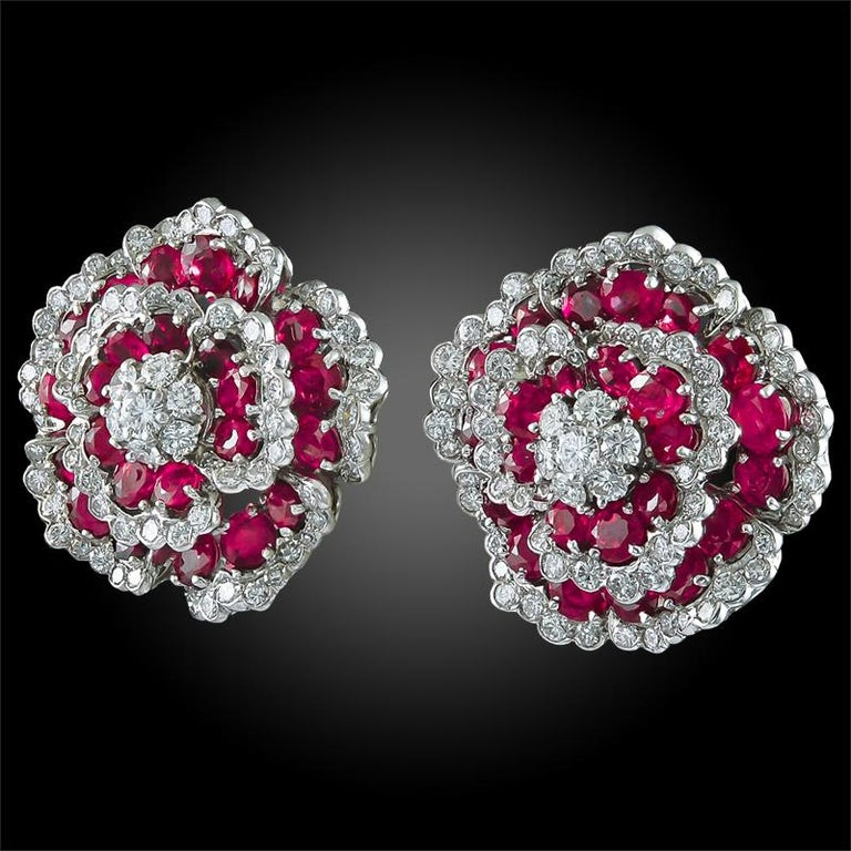 A divine pair of vintage ear clips by Van Cleef & Arpels, dating back to the 1980s, both in the shape of a flowerhead. Each flowerhead centers upon a circular-cut diamond cluster surrounded by oval-cut ruby petals, enhanced by circular-cut diamond