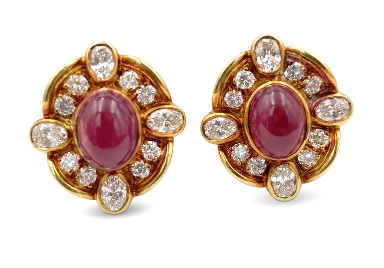Vintage Van Cleef & Arpels diamond and ruby ear clips made in 18 karat yellow gold. The earrings center on cabochon ruby stones weighing an approximate 6.40 carat total surrounded by oval and round brilliant cut diamonds (F-G in color, VS clarity)