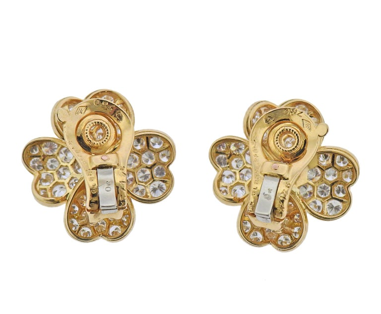 Pair of 18k gold flower earrings by Van Cleef & Arpels, with approx. 3.60ctw in F/VVS diamonds and center rubies. Earrings are 21mm x 20mm. Marked: 750, Van Cleef & Arpels, M3176, or 750. Weight - 9 grams.