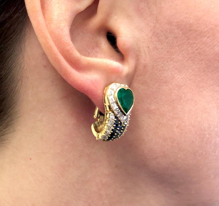 VAN CLEEF & ARPELS Heart Emerald Sapphire Diamond Earrings in 18k Yellow Gold. A pair of vintage Van Cleef & Arpels on-the-ear clips, featuring vivid heart-shaped emeralds surrounded by a halo of white diamond baguettes, with cascading trails of