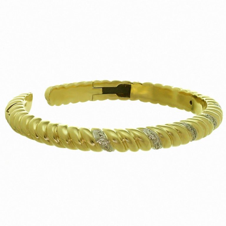 This classic vintage Van Cleef & Arpels hinged cuff bangle bracelet is crafted in 18k yellow gold and accented with brilliant-cut round G-H VS1-VS2 diamonds of an estimated 0.70 carats, set in white gold. Circa 1970s. Measurements: 0.23