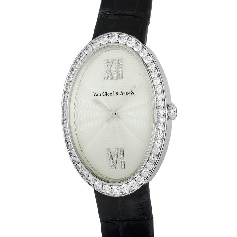 This Van Cleef & Arpels watch comes with a diamond-set 18K white gold case that is presented on a black leather strap, secured on the wrist with a diamond-set tang buckle. The dial features central hours and minutes, and boasts diamond-set Roman VI