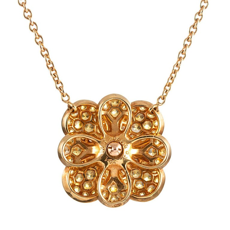 Pear-shaped petals of 18 karat yellow gold are embellished with yellow sapphires and fashioned into a flower, it's center punctuated with a cluster of white diamonds. The esteemed house of Van Cleef & Arpels is celebrated for its exceptionally