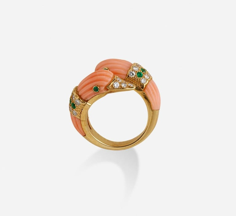 A beautiful yellow gold pinky ring presenting two duck heads, carved and scalloped in pink coral, the beaks, eyes and neck set with brilliant-cut diamonds and emeralds.  Ring size : 18.68 x 23.08 x 7.09 mm, (0.735 x 0.908 x 0.279 inch)  Total weight