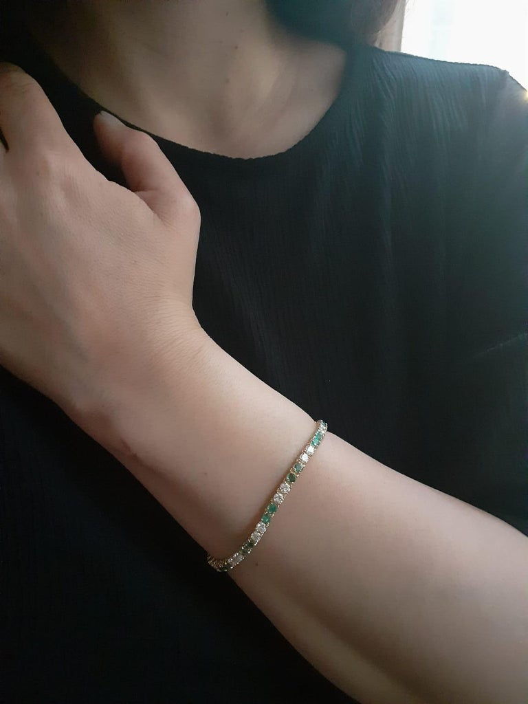 An elegant emerald and diamond line bracelet set in 18 karat yellow gold, by Van Cleef & Arpels  This exceptional bracelet is composed of a beautifully balanced combination of alternating round brilliant cut emeralds and diamonds; all of which are