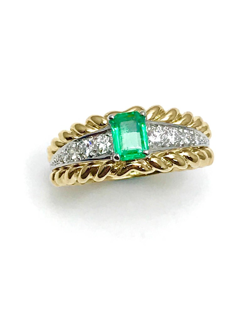 A gorgeous Van Cleef & Arpels Emerald and Diamond ring.  The .50 carat Emerald is prong set, with four diamonds to each side in platinum, between a braided gold frame, creating a split shank.  The Diamonds are round brilliant cut and have a total
