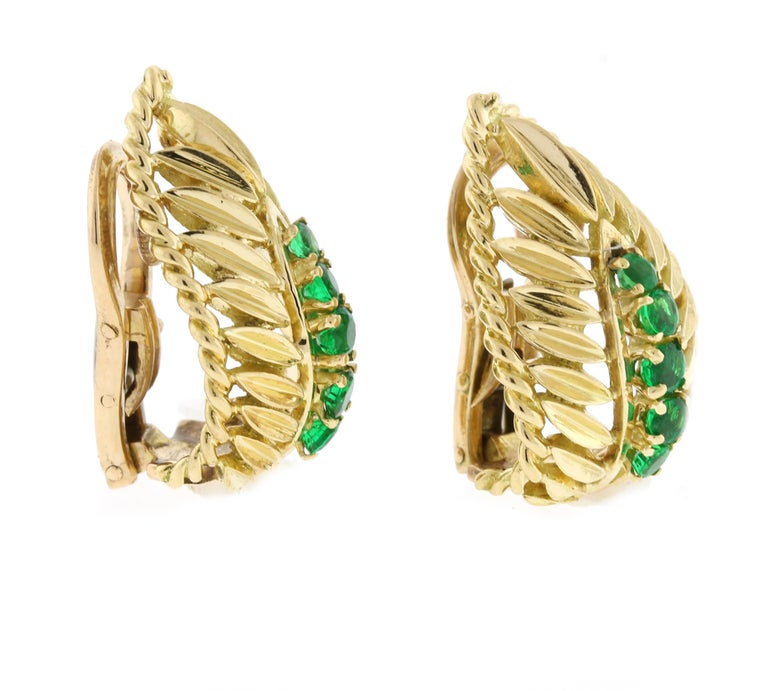 From Van Cleef & Arpels a pair of emerald and 18 karat gold emerald earclips.  The earrings are comprised of 10 vibrant green gem emeralds weighing approximately .50 carat. The earrings measure  7/8th of an inch high and 1/2inch across