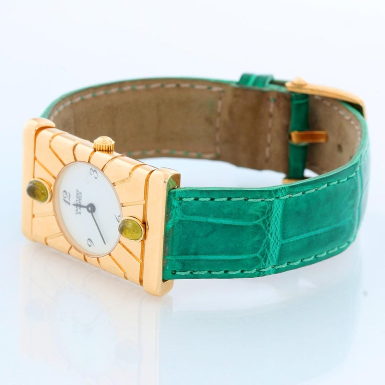 Van Cleef & Arpels Façade 18K Yellow Gold Vintage Watch - Quartz. 18K Yellow Gold  (22 mm x 33 mm) with green tourmaline on bezel. White dial with  Arabic numerals. Green strap with Van Cleef & Arpels tang buckle . Pre-owned with custom box .