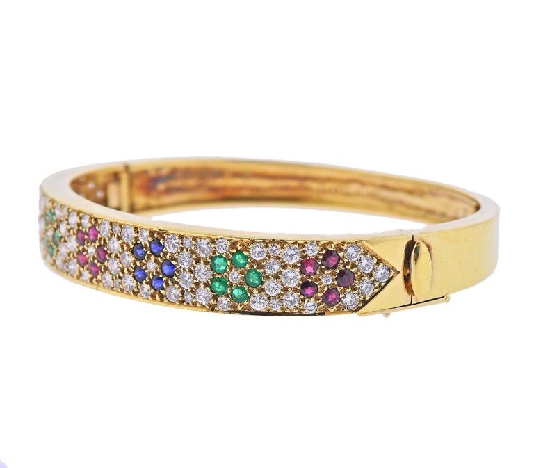 18k yellow gold bangle bracelet by Van Cleef & Arpels, featuring flowers, set in rubies, emeralds, sapphires and surrounded with approx. 2.40ctw in diamonds. Bracelet will fit approx. 7