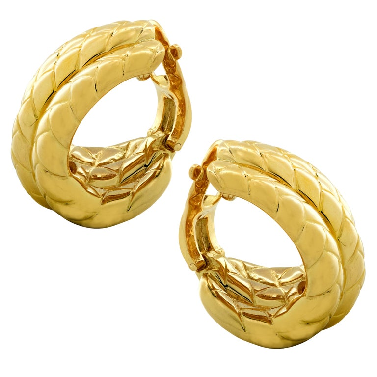 Van Cleef & Arpels vintage hoop earrings, finely crafted in France in 18 karat yellow gold, featuring three hoops detailed with lines creating a braided effect. These clip on earrings measure 1 inch in length and .73 of an inch at their widest part