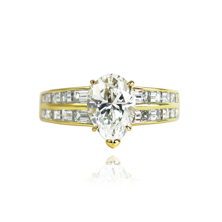 This exceptional ring from the house of Van Cleef and Arpels features a GIA certified 2.00 carat pear modified brilliant cut diamond of E color and VS1 clarity. Set in a 18K yellow gold setting with 20 straight baguettes, this scintillating piece is
