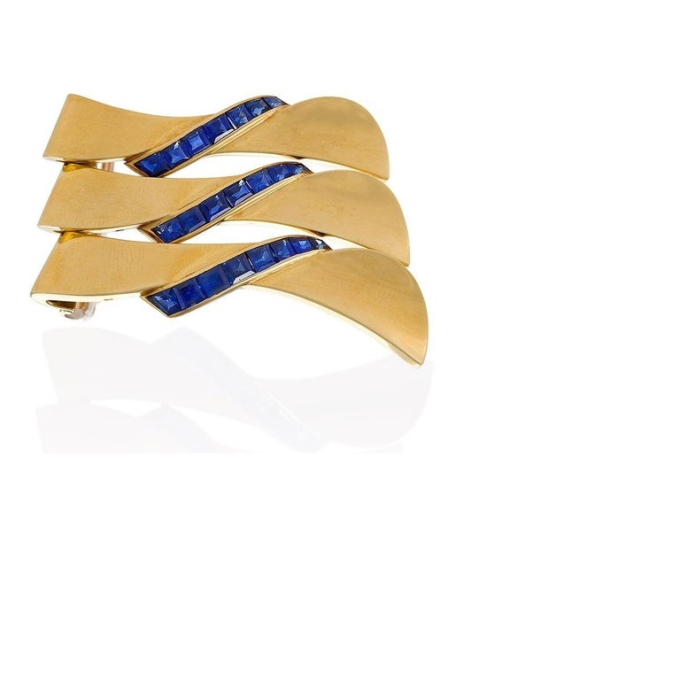 A convertible French 18 karat gold clip brooch with calibre-cut sapphires by Van Cleef & Arpels. The brooch, convertible into a set of three, is highlighted by channel-set lines of 22 calibre-cut sapphires with an approximate total weight of 2.90