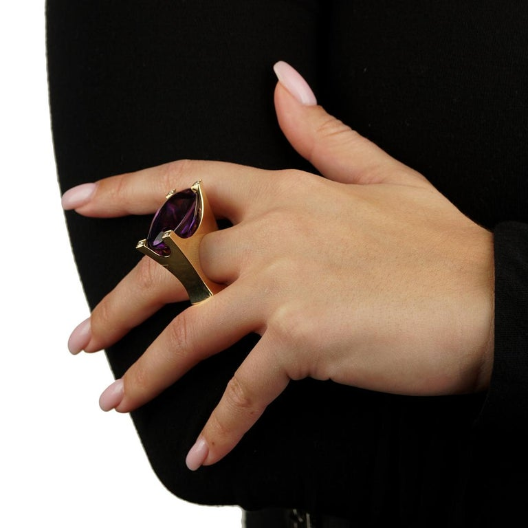 A fabulous Van Cleef and Arpels cocktail ring featuring a vivid amethyst encased by 4 of the finest Van Cleef and Arpels round brilliant cut diamonds in 18k yellow gold. The ring measures a size 6 1/4  Weight : 45.8 grams