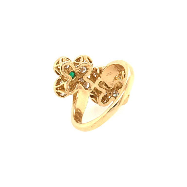 An 18 karat yellow gold, diamond and emerald Trefle Flower Ring. Van Cleef & Arpels. Circa 1980. Of bypass design, with two pave set diamond flower heads, each set with a cabochon emerald measuring approximately 3.7mm. Thirty two (32) diamonds weigh