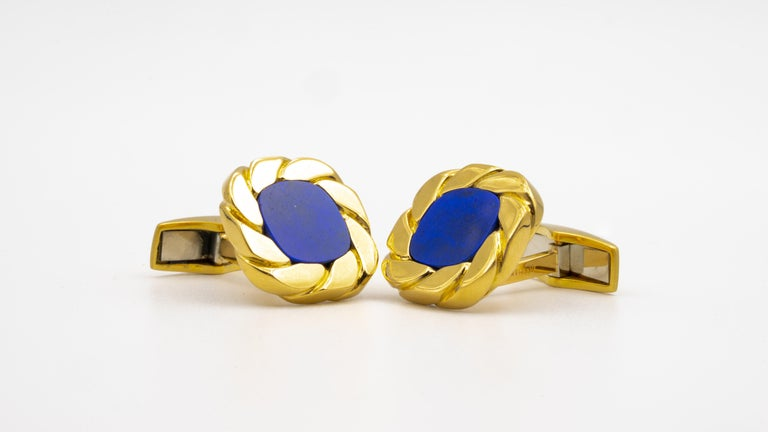 Van Cleef & Arpels pair of 18KT yellow gold cufflinks with 2 cushion-shaped lapis centers within curb link frames.  Whale Backs Stamp: Signed VCA, Germany, no. 12V666.1,  Weight: 25.7 grams Diameters: 3/4 inch