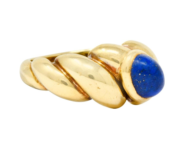 Centering a bezel set oval lapis cabochon measuring approximately 7.3 x 5.4 mm, ultramarine blue in color with flecks of gold pyrite  Completed by a dynamically twisted band with a polished gold finish  Maker's mark for Van Cleef & Arpels and