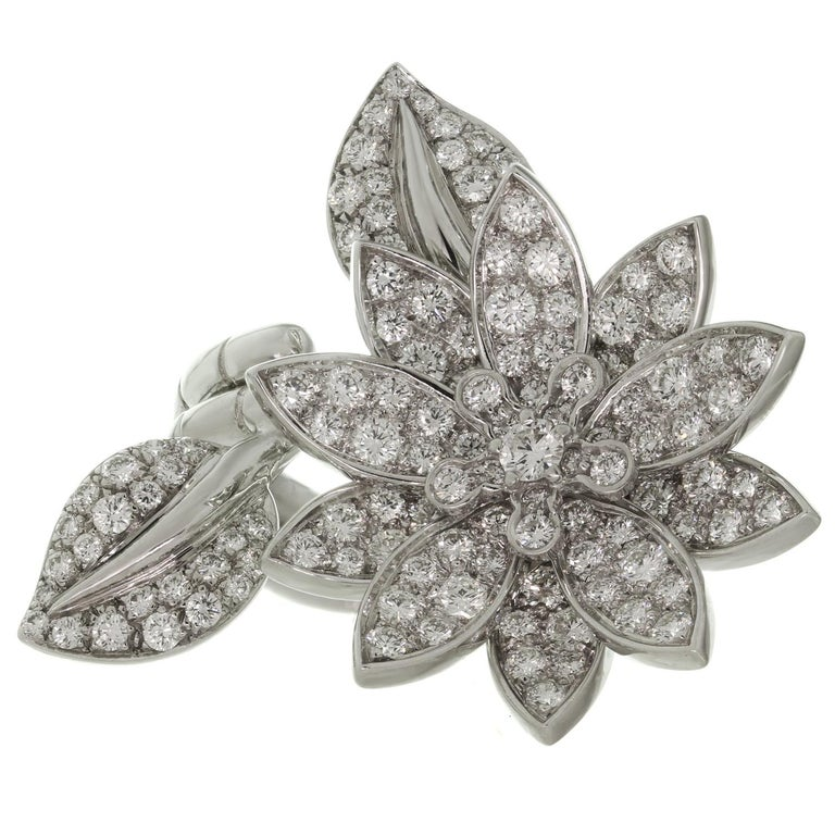 This fabulous Van Cleef & Arpels ring is crafted in 18k white gold and features a gorgeous lotus flower design set with 127 brilliant-cut round D-E VVS1-VVS2 diamonds of an estimated 2.20 carats. This between-the-finger ring can be worn on either