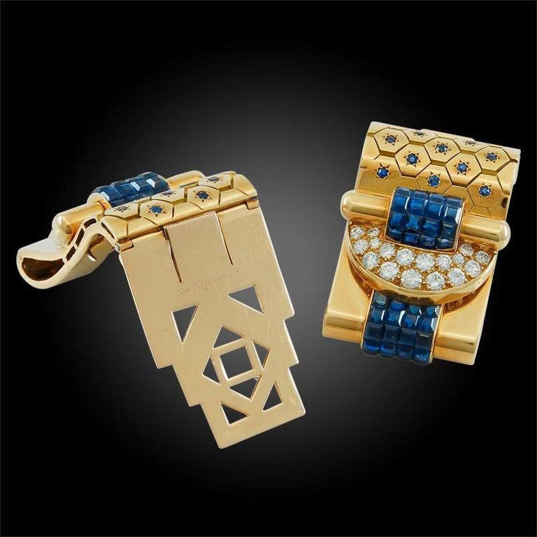 """Comprising a 1940s French Retro pair of """"Ludo-Hexagone""""  18 karat yellow gold double clips by Van Cleef & Arpels, of a stylized buckle design, finely crafted with round brilliant cut diamonds and mystery set  sapphires in a honeycomb and etched star"""