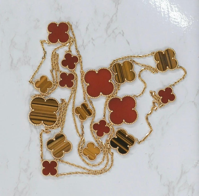 Very Rare Van Cleef & Arpels 18k Gold Tiger Eye Carnelian 16 Motif Magic Alhambra Necklace. This necklace comes with a Van Cleef & Arpels Box   Dandelion Antiques CodeAT-12654 Brand                                Van Cleef & Arpels Model