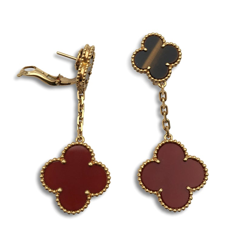Authentic Van Cleef & Arpels 'Magic Alhambra' earrings crafted in 18 karat yellow gold featuring two different-sized Alhambra clover motifs; one made from carnelian and the other with tigers eye stone. Signed VCA, Au750, with serial number. The