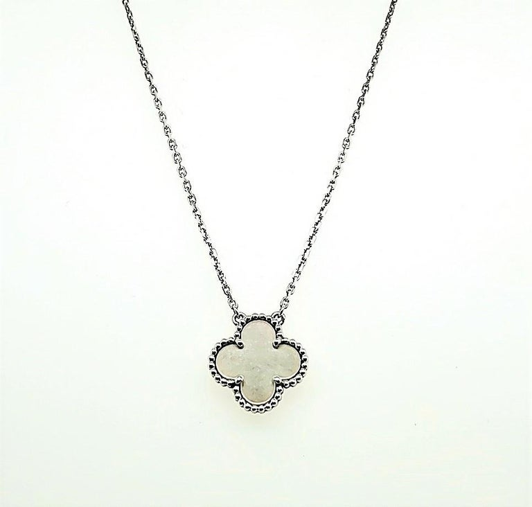 Authentic Van Cleef & Arpels pendant necklace crafted in 18 karat white gold and featuring a clover-shaped pendant crafted in mother of pearl.  The length of the chain is adjustable and can be worn at 7 or 8 inches in length.  The pendant measures
