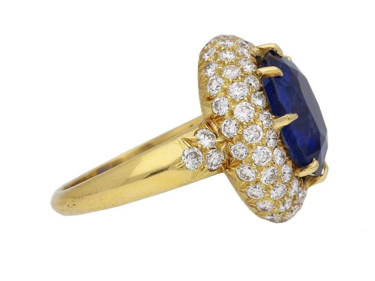 Van Cleef & Arpels Burmese sapphire and diamond cluster ring. Set with a natural unenhanced oval old cut Burmese sapphire to centre in an open back claw setting with an approximate weight of 5.56 carats, encircled by three rows of round brilliant