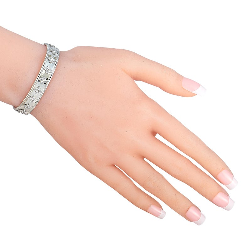 """The Van Cleef & Arpels """"Perlée"""" bracelet is made of 18K white gold and boasts clover motifs embellished with diamonds. The bracelet weighs 31.7 grams and measures 6.65"""" in length.  This jewelry piece is offered in estate condition and includes the"""
