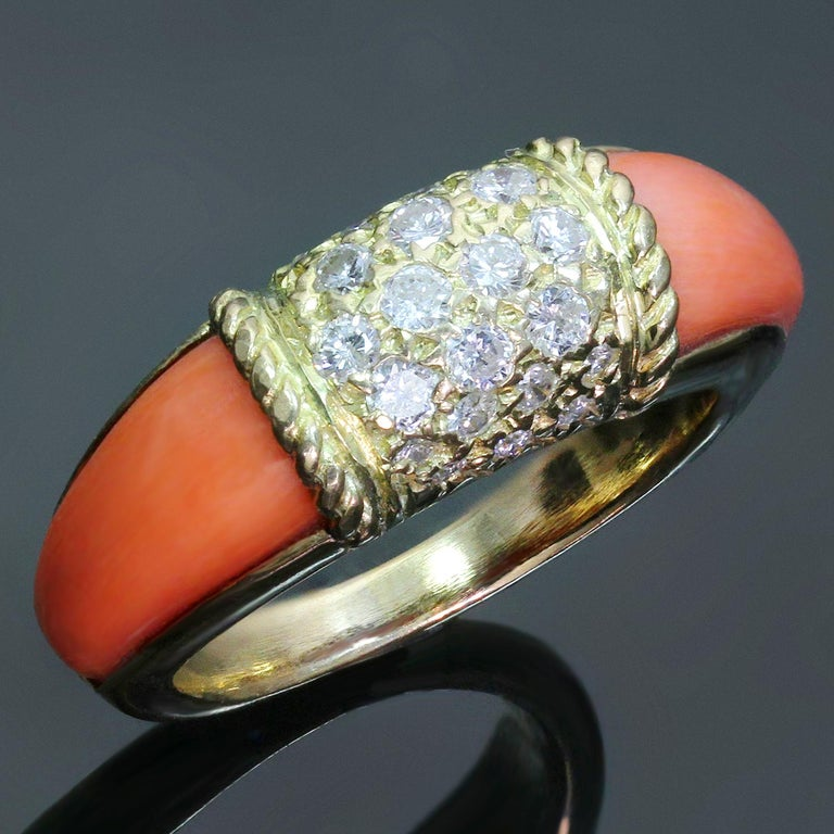 This rare vintage Van Cleef & Arpels ring from the classic Philippine collection is crafted in 18k yellow gold and features an estimated 0.50 carats of natural round diamonds pave-set in the center complemented with pink corals on the sides. Circa