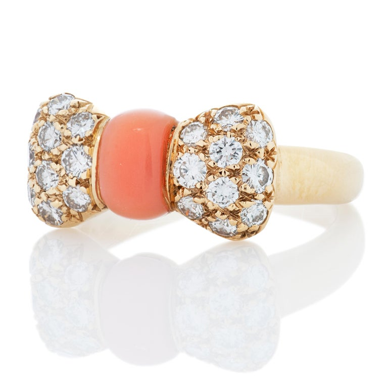Van Cleef & Arpels pink coral and diamond bow ring.  This ring contains 20 round diamonds totaling approximately 0.40 carat with estimated E-F color and VS clarity.   3.88 grams, size 3. Stamped