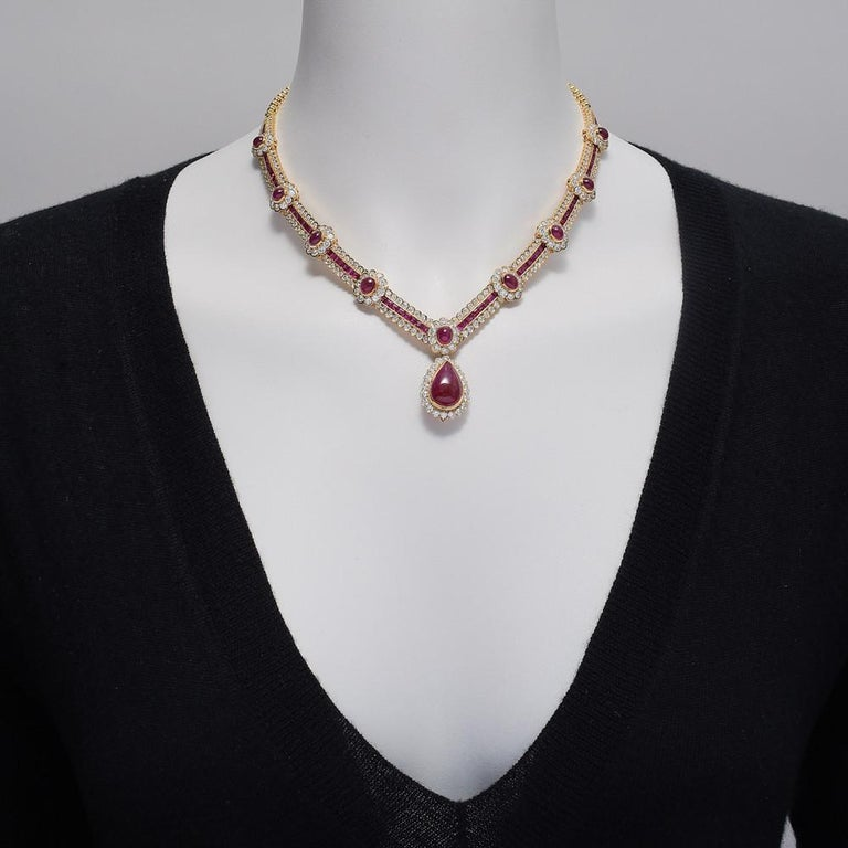 Vintage ruby and diamond necklace, the front composed of a graduated series of clusters each set with a cabochon ruby surrounded by round brilliant-cut diamonds and stationed along a calibre-cut ruby and round brilliant-cut diamond band, centering a