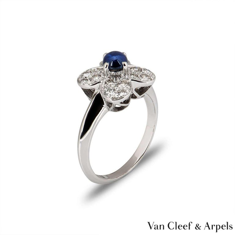 A beautiful 18k white gold Van Cleef & Arpels diamond ring from the Alhambra collection. The central flower motif is set with a single claw set blue cabochon cut sapphire. The surrounding petals of the flower are pave set with round brilliant cut