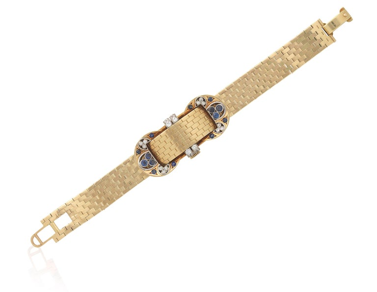 A chic retro mystery watch-bracelet by Van Cleef & Arpels in 18 karat yellow gold, embellished with round brilliant cut sapphires and old cut diamonds. The gold case opens to reveal a watch of manual movement. Made in New York, circa 1940.  Length