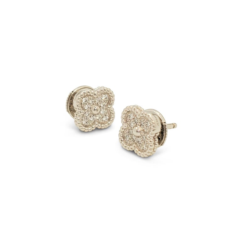 Authentic Van Cleef & Arpels 'Sweet Alhambra' earrings crafted in 18 karat white gold centering on a clover motif set with an estimated 0.16 carats total of round brilliant cut diamonds (E-F color, VS clarity). Signed VCA, Au750, with serial number