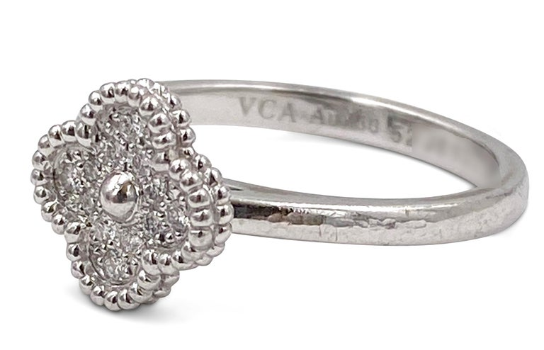 Authentic Van Cleef & Arpels 'Sweet' Alhambra' ring crafted in 18 karat white gold and set with an estimated 0.12 carats of round brilliant cut diamonds (F-G color, VS clarity).  The clover motif measures approx. 9mm x 9mm. Ring size 6. Signed VCA,