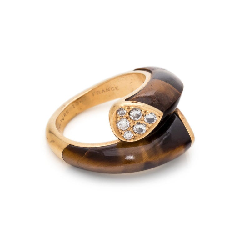 This 18K yellow gold and diamond ring features approximately 0.25 carats of diamonds and tiger's eye plaques in a bypass design set in yellow gold. Size 4.75. Stamp: V. C. A. NEW - YORK 18KT. FRANCE 5V501.23 Interior is engraved: ALL MY LOVE ARNOLD
