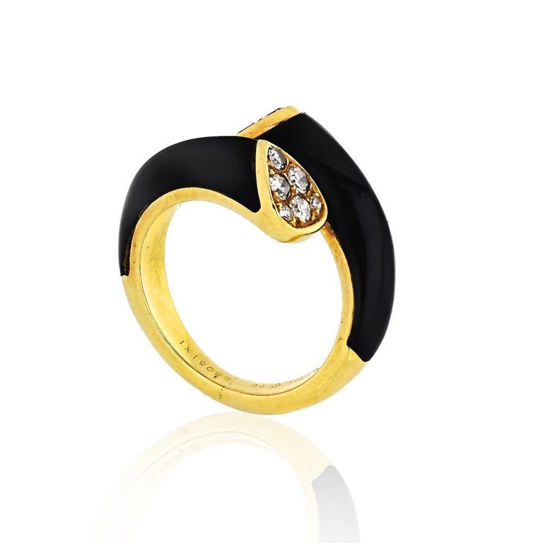 Iconic eighteen-karat yellow gold bypass ring with a polished onyx inset to the crest and six round-cut white diamonds encircled at the cusp. Total diamond weight 0.45cts.
