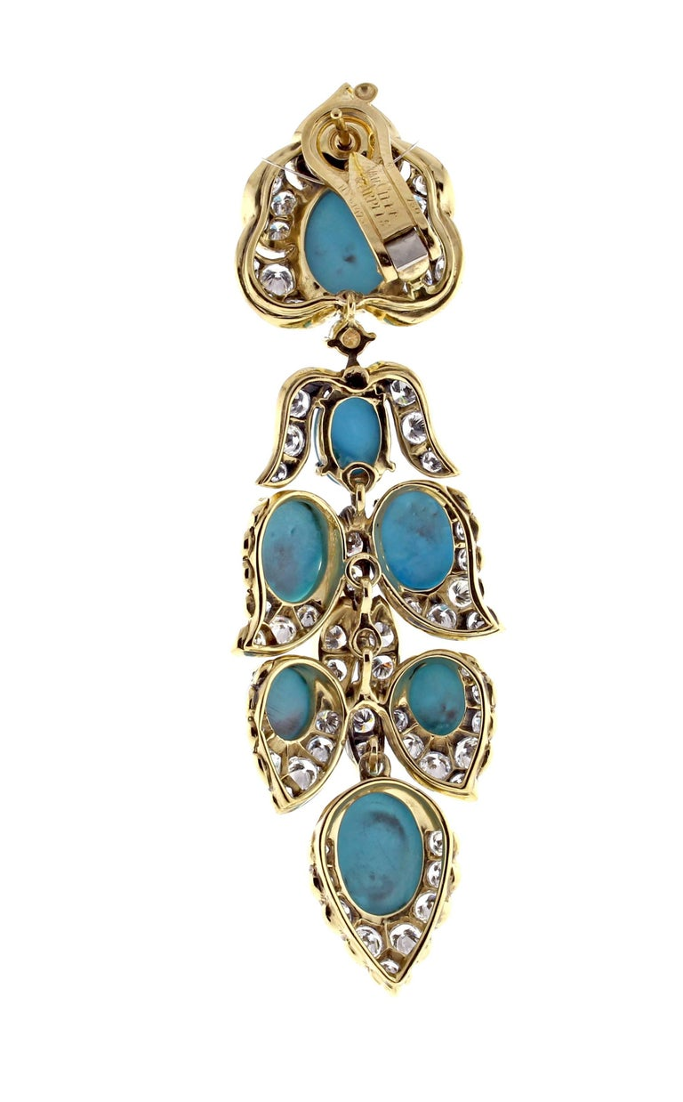 A magnificent pair of turquoise and diamond drop earrings. The earrings are 3 ¾ inches long and 7/8 inch wide. The stylized foliate designs are set with cabochon turquoise and brilliant cut diamonds. The 160 diamonds weigh approximately 13.5 carats.