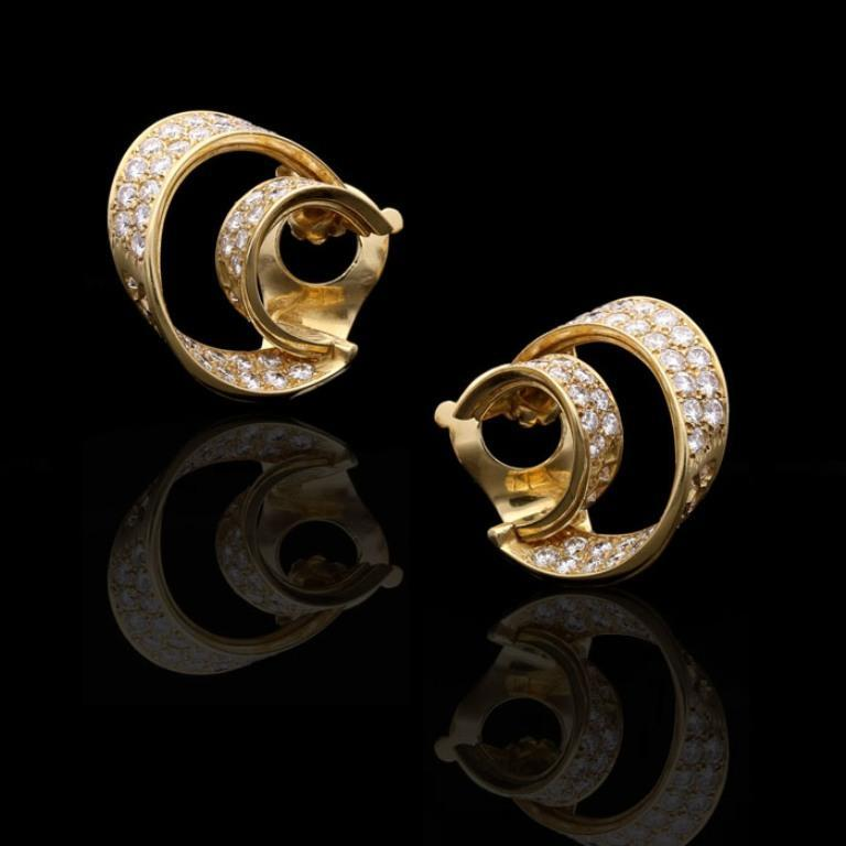 A wonderfully stylish pair of gold and diamond hoop ear clips by Van Cleef & Arpels, c.1980s, each designed as an asymmetric double ribbon-like hoop of 18ct yellow gold set throughout with round brilliant cut diamonds, with clip fittings.  114 round