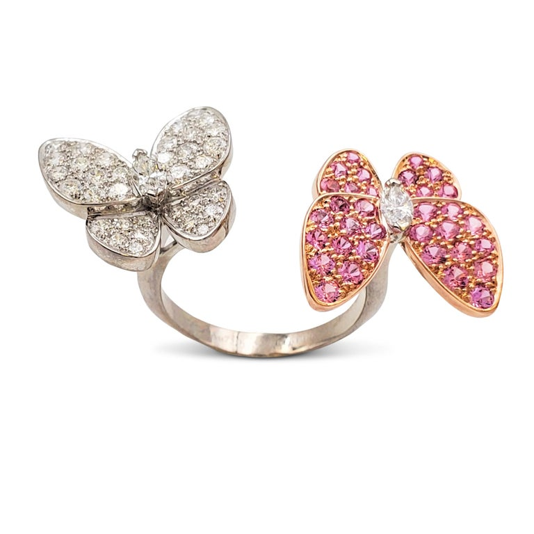 Authentic Van Cleef & Arpels 'Two Butterfly' between-the-finger ring crafted 18 karat white gold features two butterflies that combine color and asymmetry in a dazzling way. The ring is set with an estimated 0.99 carats of high-quality round