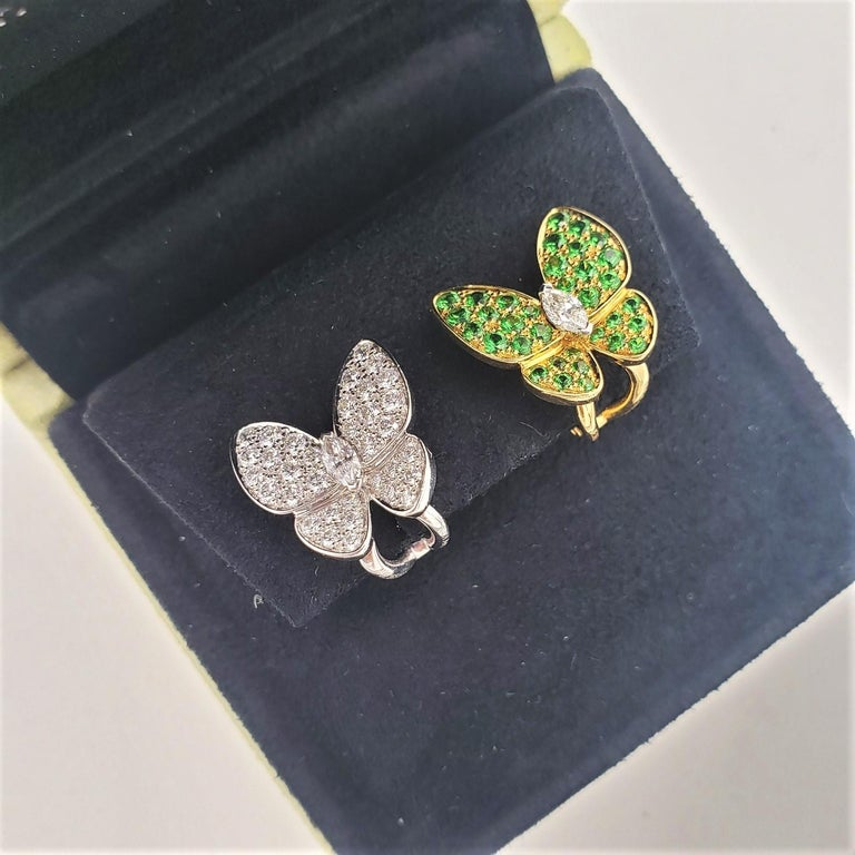 Authentic Van Cleef & Arpels 'Two Butterfly' earrings crafted in 18 karat yellow and white gold combine color and asymmetry in a dazzling way. One earring is crafted in white gold and set with an estimated 1.00 carats of high-quality diamonds. The
